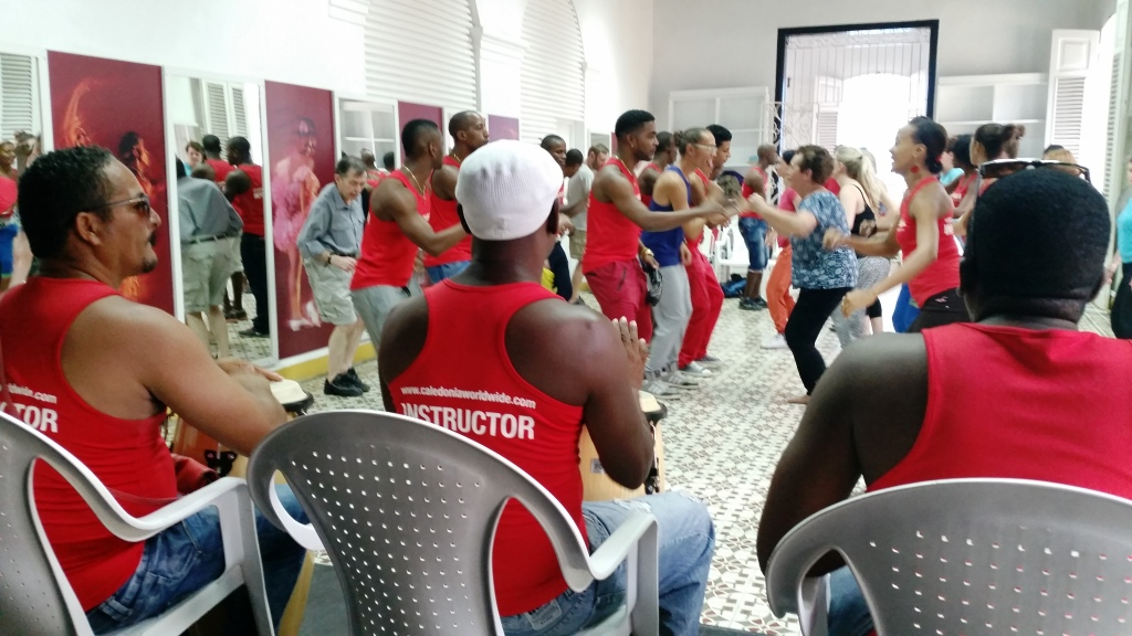 Dance teacher giving energetic dance instruction with live percussionists to group of students in red tshirts | Taking dance classes in Cuba
