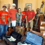 musicians in red tshirts with instruments