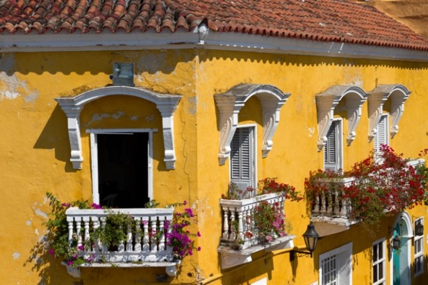 Colourful yellow walls and balcony with flowers