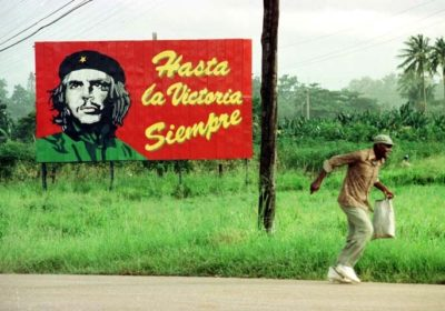 man running in front of billboard Cuba