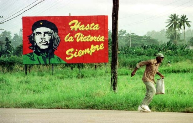 man running in front of billboard Cuba