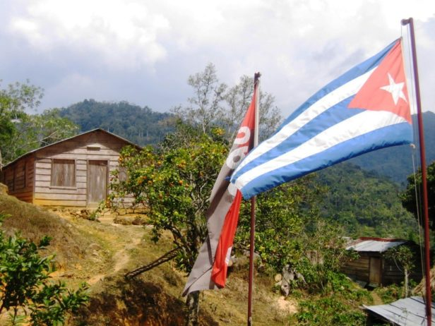 wooden hut in the mountains with 2 flags in front