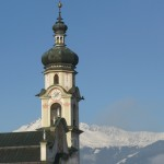 Church tower and snowy mountains