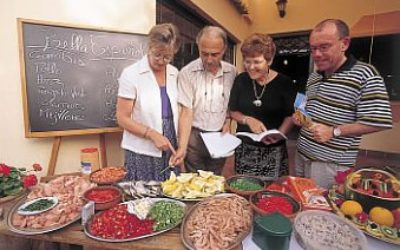 four older people with food on a table