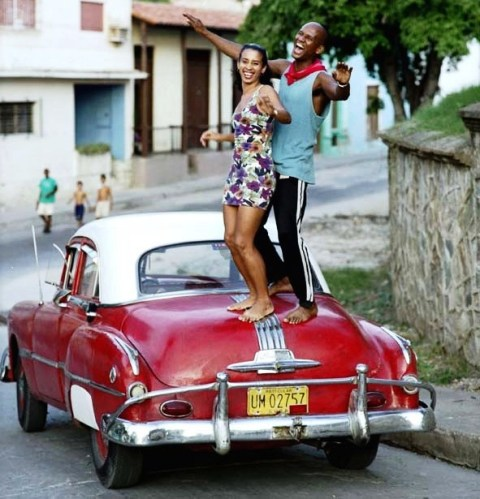 couple dancing on top of an old car