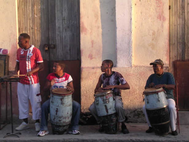 four Afro-Cuban musicians playing music in the street