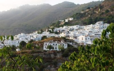 view of white houses in a mountain village surrounded by green landscape