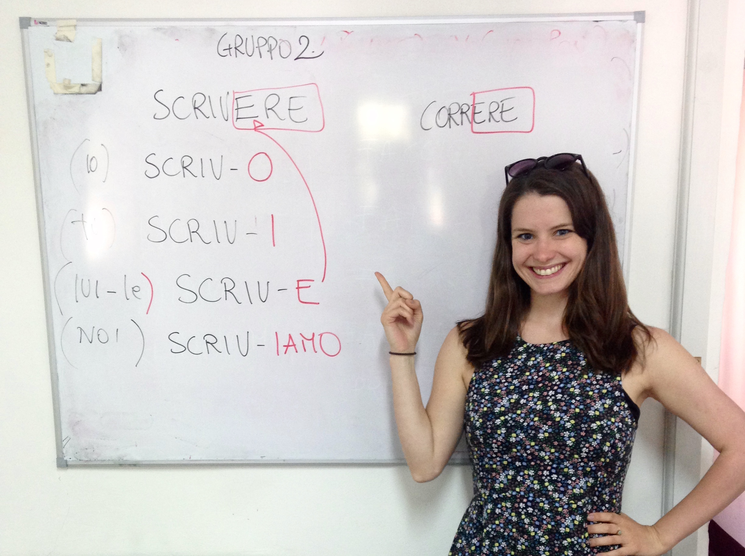 Language student pointing to board of Italian verbs during Italian Language course