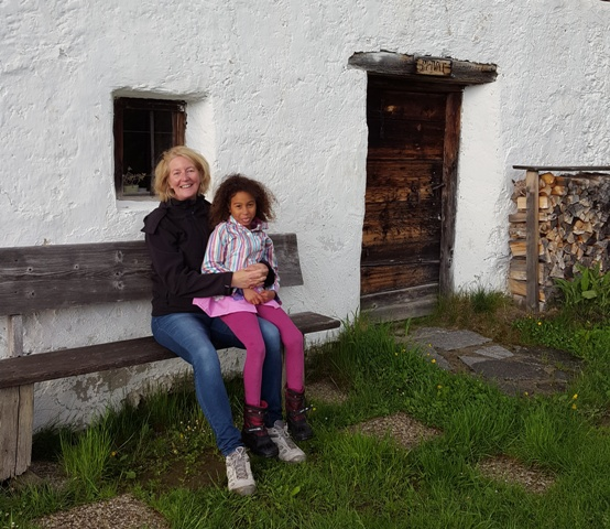 Woman and girl sitting on bench outside farmhouse