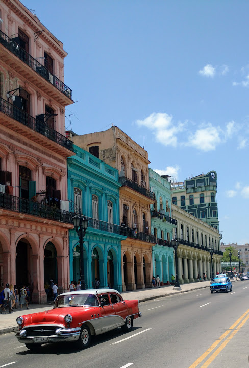 A red vintage car driving along an avenue of brightly coloured buildings in Havana, Cuba
