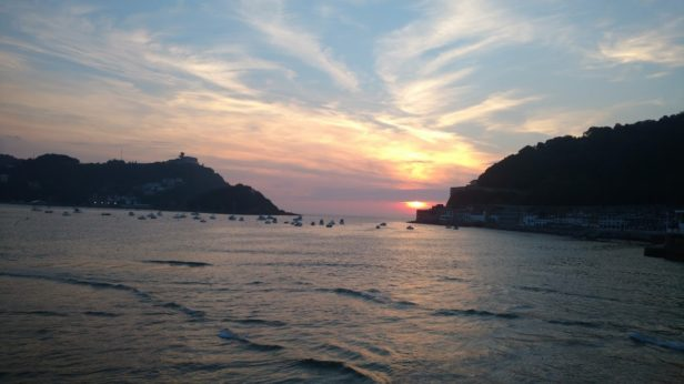 Red sun setting over the bay with a few sail boats in San Sebastian, Basque Country