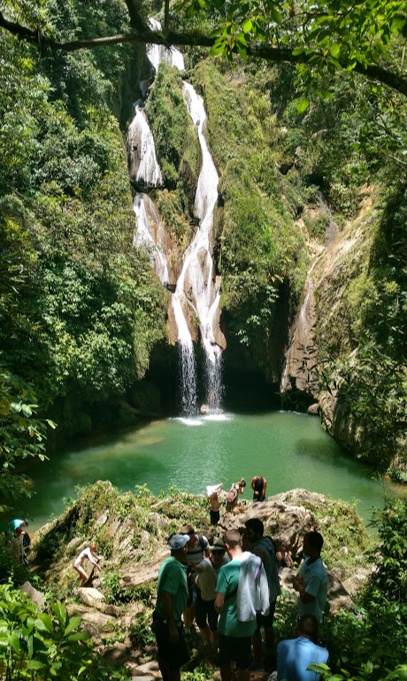 A group of people hiking down to a large natural pool of water with a waterfall pouring in from the green mountainside. Vegas Grande Waterfall in Topes de Collantes National Park, Cuba