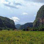 A view of lush green landscape in Viñales Valley, Cuba. Small, red roofed farm huts sit at the foot of a group of towering limestone structures