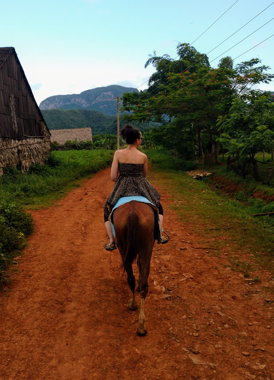 A view of a girl trekking on horseback through Viñales Valley on a rust red dirt track with green mountains in the background. Viñales, Western Cuba