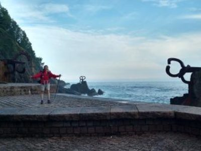 A female walker stands in front of wind comb sculptures on the rocky coastline, San Sebastian