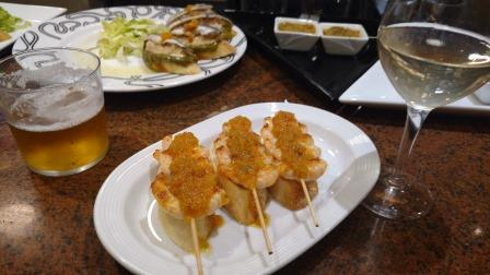 Three prawn tapas sitting on a plate with a glass of wine and glass of beer in view, San Sebastian