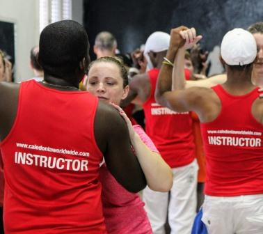 Girl dancing with dance teacher in red vest top. Other dance couples in the background