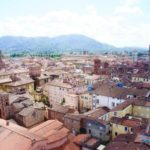 View overlooking the historic city of Lucca with many terracotta roofs and green mountains in the background