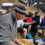 Austrian man cutting cheese for students to try