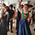 A group of boys and girls in traditional Austrian outfits dancing