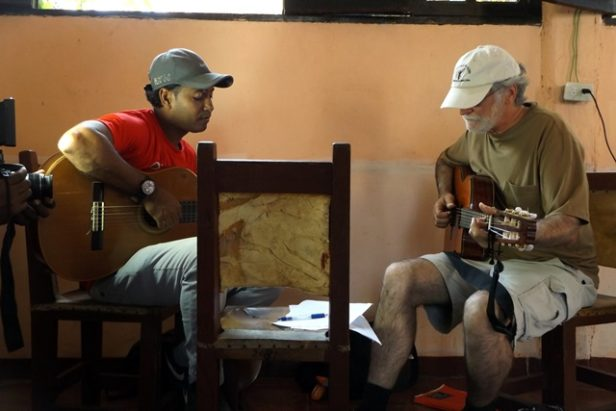 Two men sitting with guitars learning music