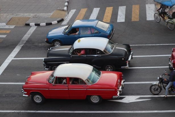 Three brightly painted vintage cars driving on the streets of Havana