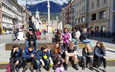 Group of teenagers sitting in Innsbruck town centre