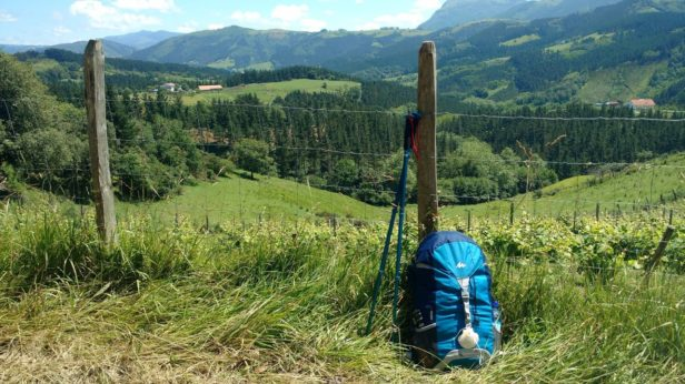 A blue rucksack and walking poles in front of a green landscape of fields and mountains in the Basque Country