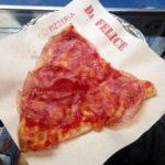 A slice of salami pizza on a napkin
