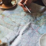 A map on a table with a coffee on top of it and a hand with a pen